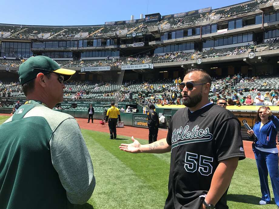 Former A's catcher Ramon Hernandez, left, catches up with head grounds keeper Clay Wood before Saturday's game. Photo: Susan Slusser, The Chronicle