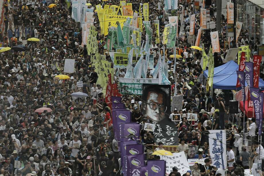Protesters carry an image of detained Chinese Nobel Peace laureate Liu Xiabo as they march during the annual pro-democracy demonstration in Hong Kong. Many say China is violating Hong Kong's autonomy. Photo: Vincent Yu, Associated Press
