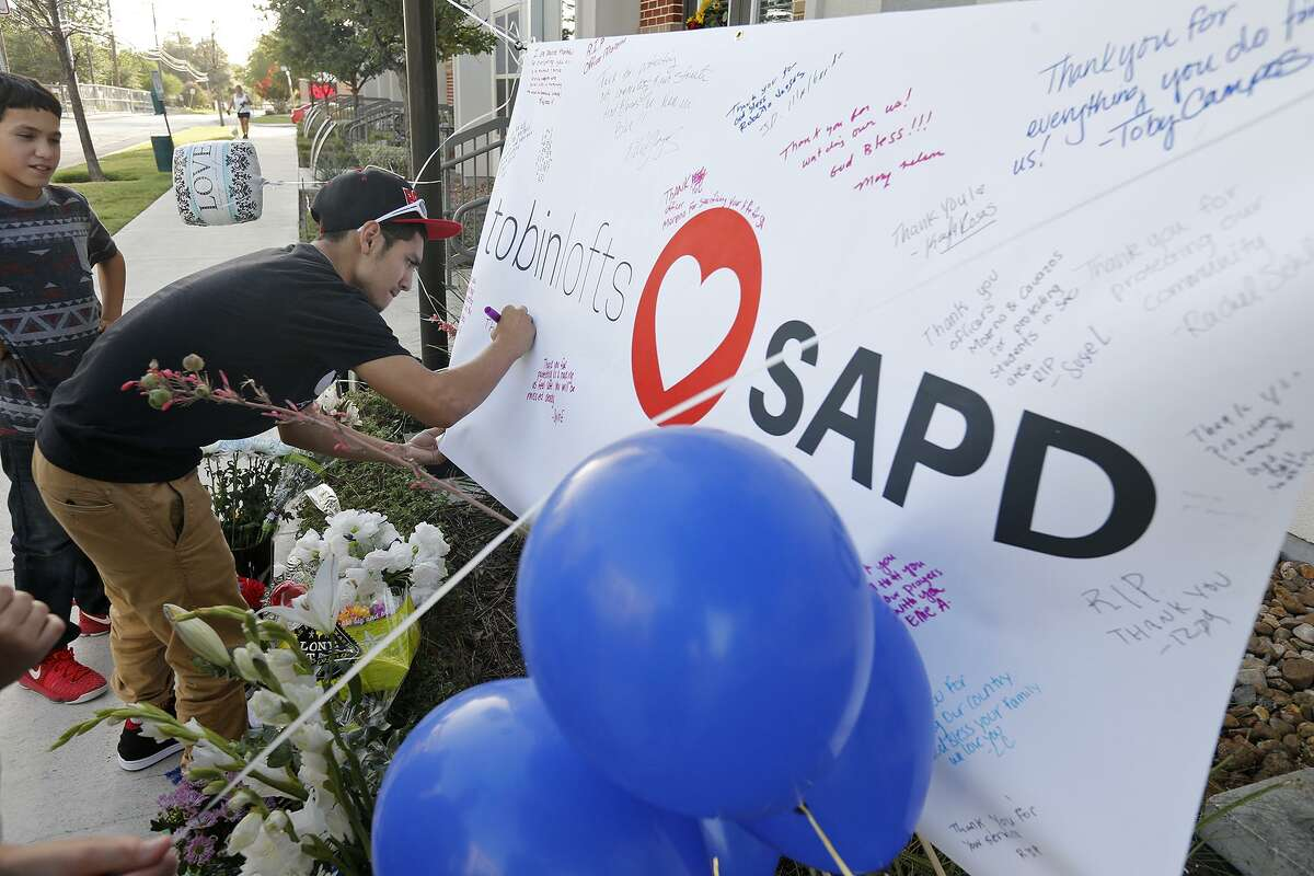 Anthony Arriola, 14, (left) watches as his brother Christian Arriola, 15, signs a banner at a memorial for SAPD Officer Miguel Moreno, 32, who was pronounced dead at 11:11 a.m. Friday June 30. Moreno was one of two officers shot in the 200 block of W. Evergreen St. near San Antonio College on Thursday June 29.