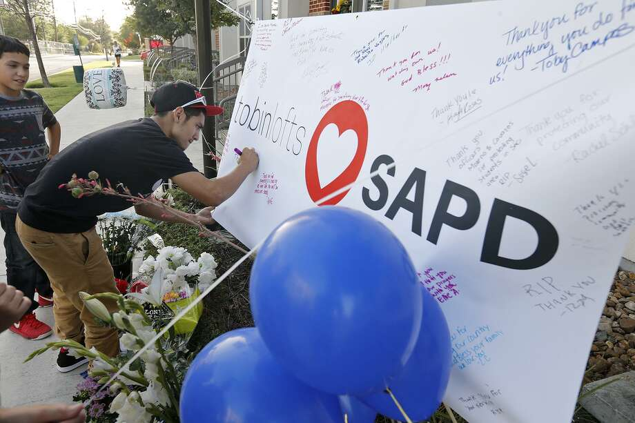 Anthony Arriola, 14, (left) watches as his brother Christian Arriola, 15, signs a banner at a memorial for SAPD Officer Miguel Moreno, 32, who was pronounced dead at 11:11 a.m. Friday June 30. Moreno was one of two officers shot in the 200 block of W. Evergreen St. near San Antonio College on Thursday June 29. Photo: Edward A. Ornelas, Staff / San Antonio Express-News / © 2017 San Antonio Express-News