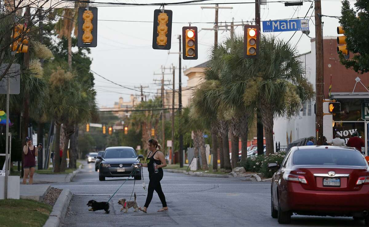 A woman walks her dogs, Friday June 30, 2017, at the intersection of N. Main Ave. and W. Evergreen St. near the area of the officer-involved shooting that occurred Thursday June 29, 2017.
