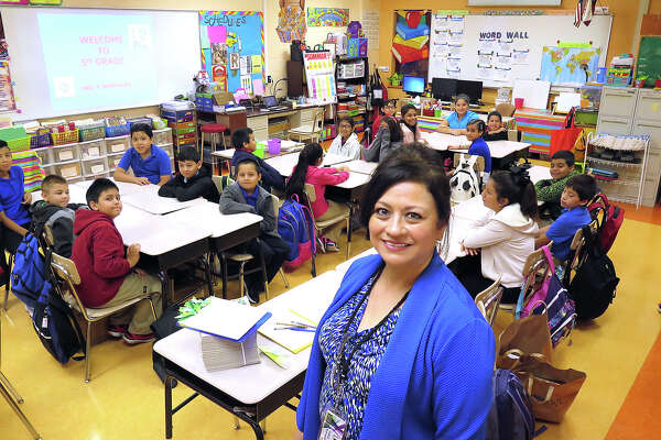 Bruni Elementary 5th grade teacher Patricia Rodriguez poses with her students Monday morning as they start the new school year.