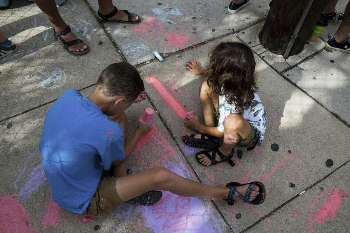 Jordan Crumpton, 11, left, and Joshua Crumpton, 6, draw with chalk while waiting to create rainbow crosswalks in honor of Pride at the intersection of Evergreen and Main streets in San Antonio, Texas on July 1, 2017.