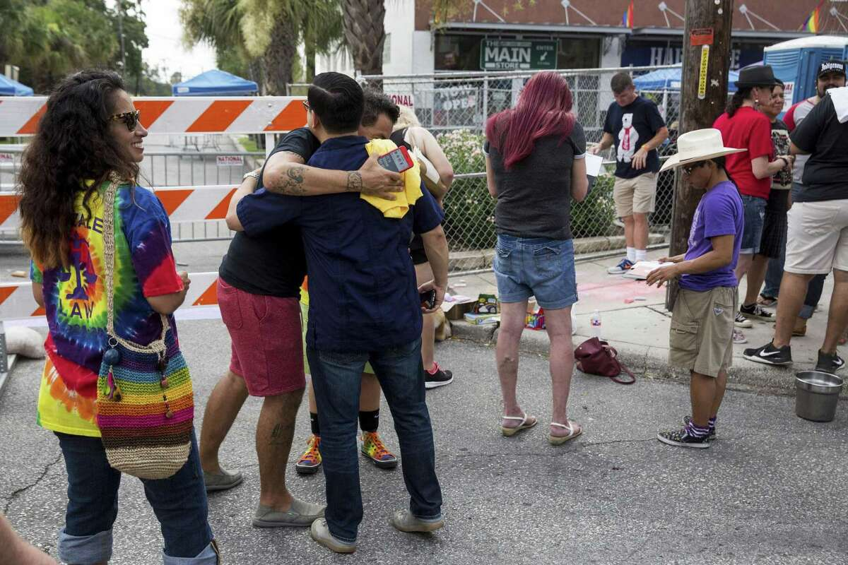 Ernesto Olivo and Diego Bernal hug before volunteers use chalk to create rainbow crosswalks in honor of Pride at the intersection of Evergreen and Main streets in San Antonio, Texas on July 1, 2017.