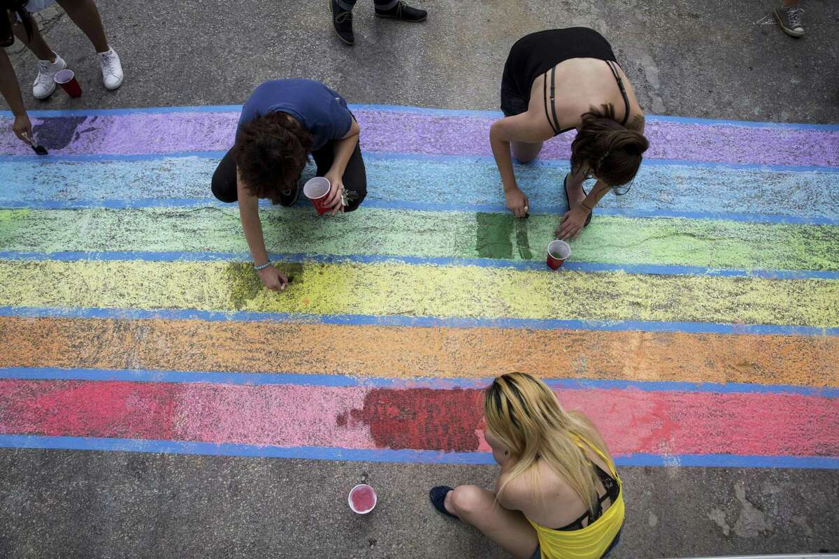 Volunteers Michelle Cowan, left, Alyssia Maynard, top right, and Alize Sanchez, bottom, use chalk to create rainbow crosswalks in honor of Pride at the intersection of Evergreen and Main streets in San Antonio, Texas on July 1, 2017.