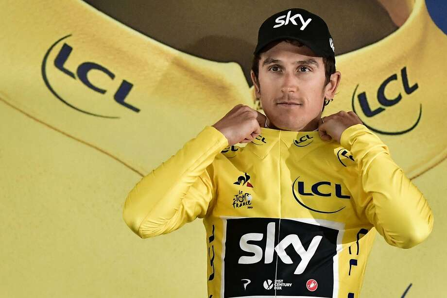 Geraint Thomas tries on his new threads — the overall leader's yellow jersey he figures to keep warm for team- mate Chris Froome. Photo: PHILIPPE LOPEZ, AFP/Getty Images