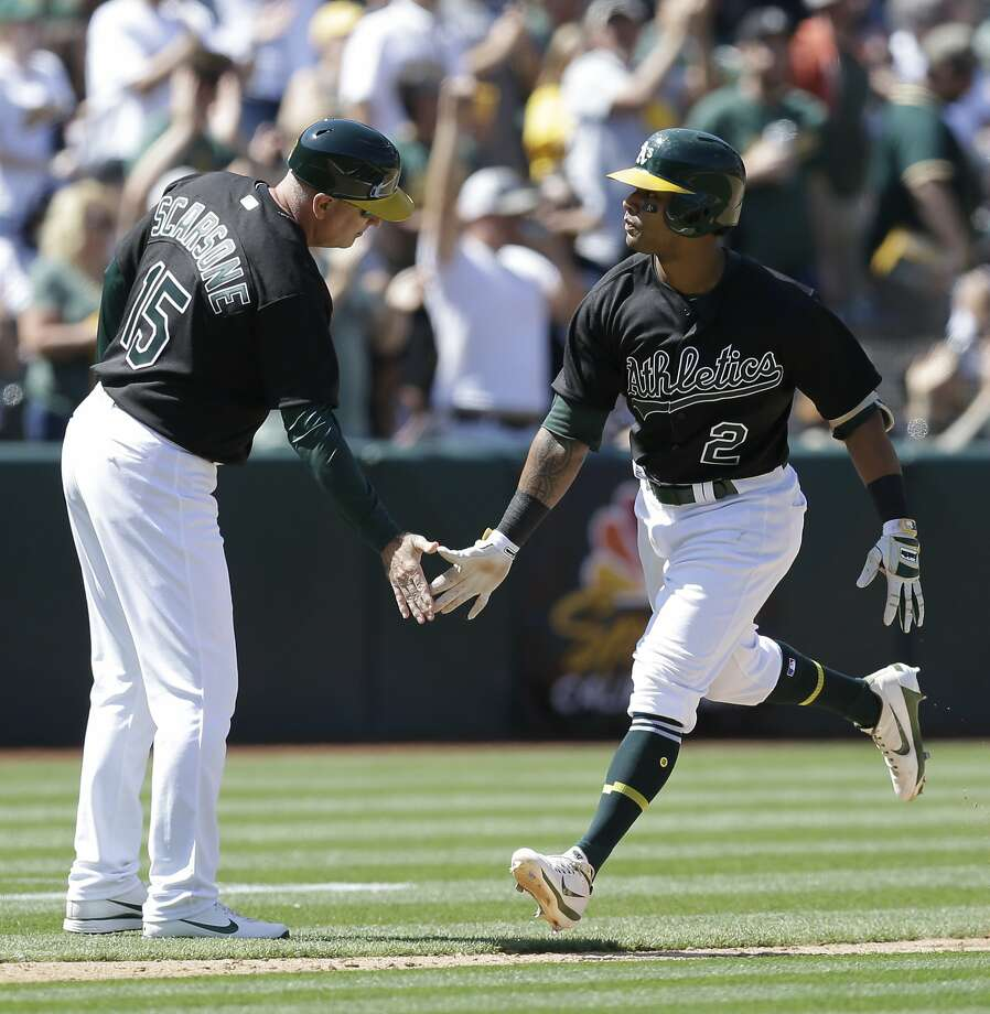 Oakland Athletics' Khris Davis, right, is congratulated by third base coach Steve Scarsone (15) after hitting a two run home run off Atlanta Braves' Arodys Vizcaino in the eighth inning of a baseball game Saturday, July 1, 2017, in Oakland, Calif. (AP Photo/Ben Margot) Photo: Ben Margot, Associated Press