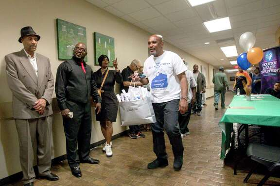 """Joseph Dowell, second from left, also known as """"Unc,"""" waits in the hall before a graduation ceremony for the Community Re-Entry Network Program, Thursday, May 18, 2017, in Houston. While in jail, Dowell was part of the """"Freedom Project,"""" which aims to help inmates struggling with addiction. After his release, he began working with the CRNP, and he will start a job with the City of Houston in a few weeks. ( Jon Shapley / Houston Chronicle )"""