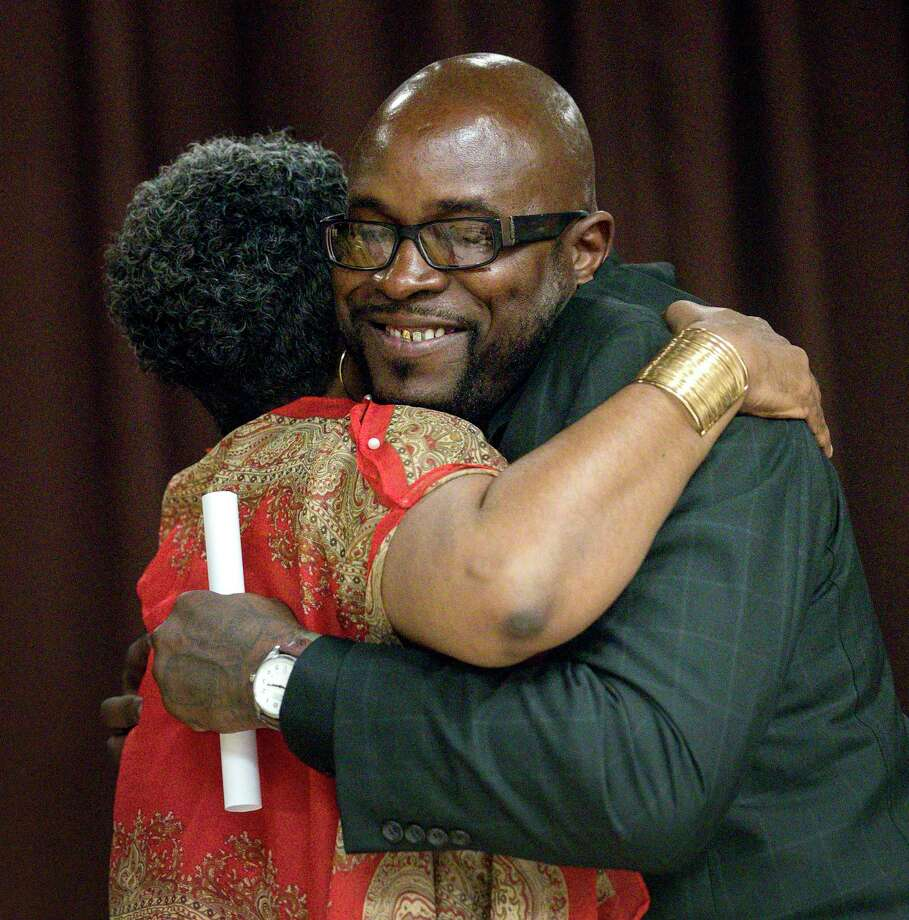 """Joseph Dowell, right, also known as """"Unc,"""" hugs Jennifer Herring, director of re-entry services at the Harris County Sheriff's Office, during a graduation ceremony for the Community Re-Entry Network Program, Thursday, May 18, 2017, in Houston. While in jail, Dowell was part of the """"Freedom Project,"""" which aims to help inmates struggling with addiction. After his release, he began working with the CRNP, and he will start a job with the City of Houston in a few weeks. ( Jon Shapley / Houston Chronicle ) Photo: Jon Shapley, Staff / © 2017 Houston Chronicle"""