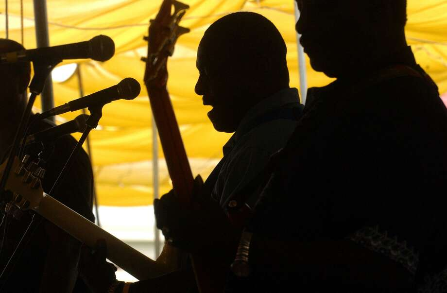 Melvin Hudnal, center, lead singer and lead guitarist of The Voices of the Mainland belts out a gospel song on the final day of the Texas Folklife Festival in June 2004. The group is a mainstay of the annual festival. Photo: San Antonio Express-News File Photo / SAN ANTONIO EXPRESS-NEWS