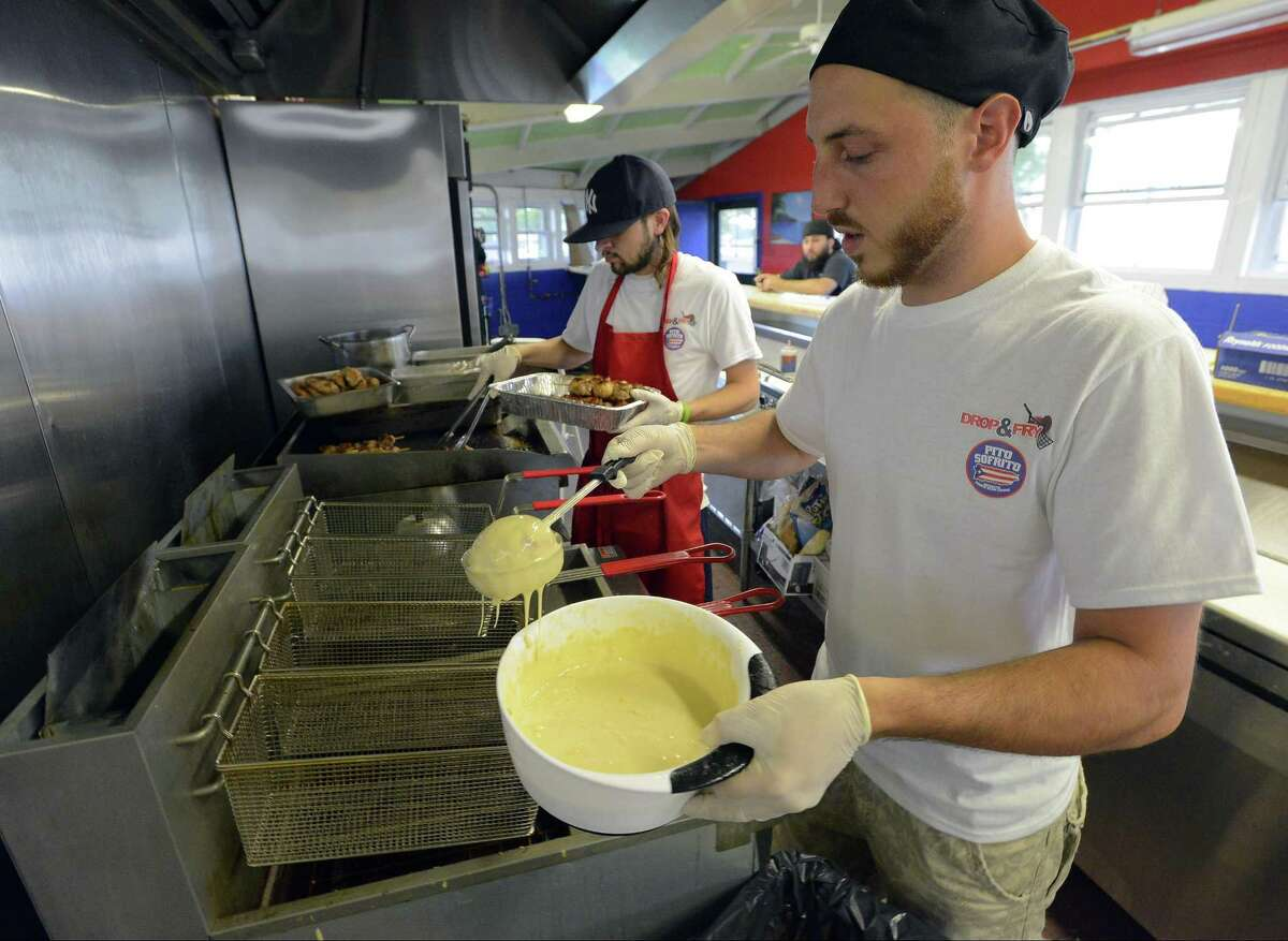 Tyler Burchard, manager of Drop & Fry, prepares an order of Fried Ice Cream for a customer of the new concession at Cummings Beach in Stamford, Conn., on Friday, June 23, 2017.