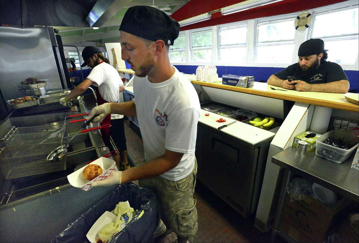Tyler Burchard, manager of Drop & Fry, pulls an order of Fried Ice Cream from the fryer he was preparing for a customer of the new concession at Cummings Beach in Stamford, Conn., on Friday, June 23, 2017.