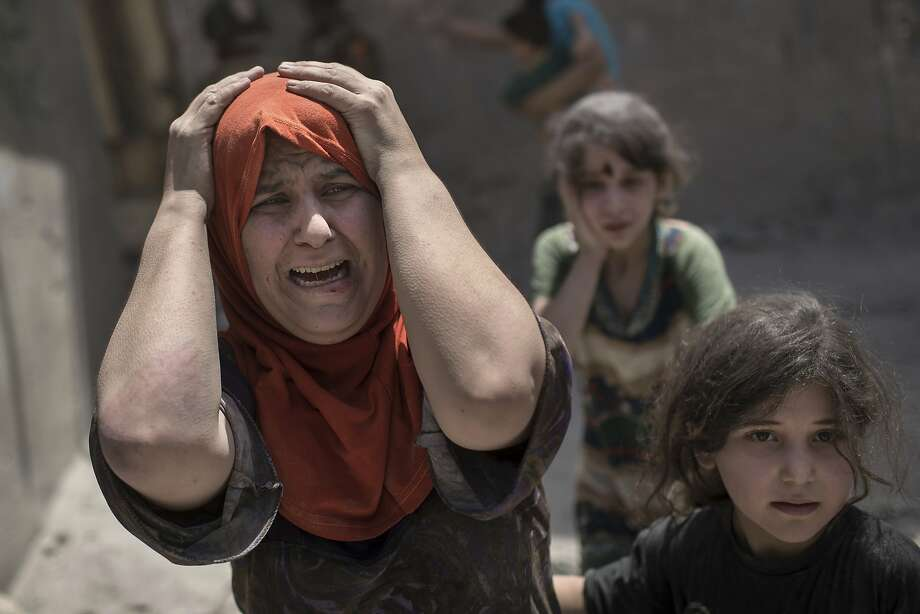 A woman screams while fleeing with her family through an alley in the Old City district of Mosul, Iraq. Photo: Felipe Dana, Associated Press