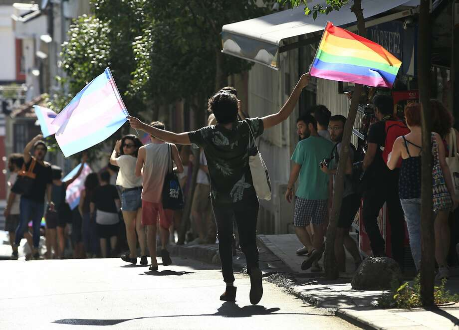 Transgender rights activists disperse to avoid detention by Turkish police officers in Istanbul. Photo: Lefteris Pitarakis, Associated Press