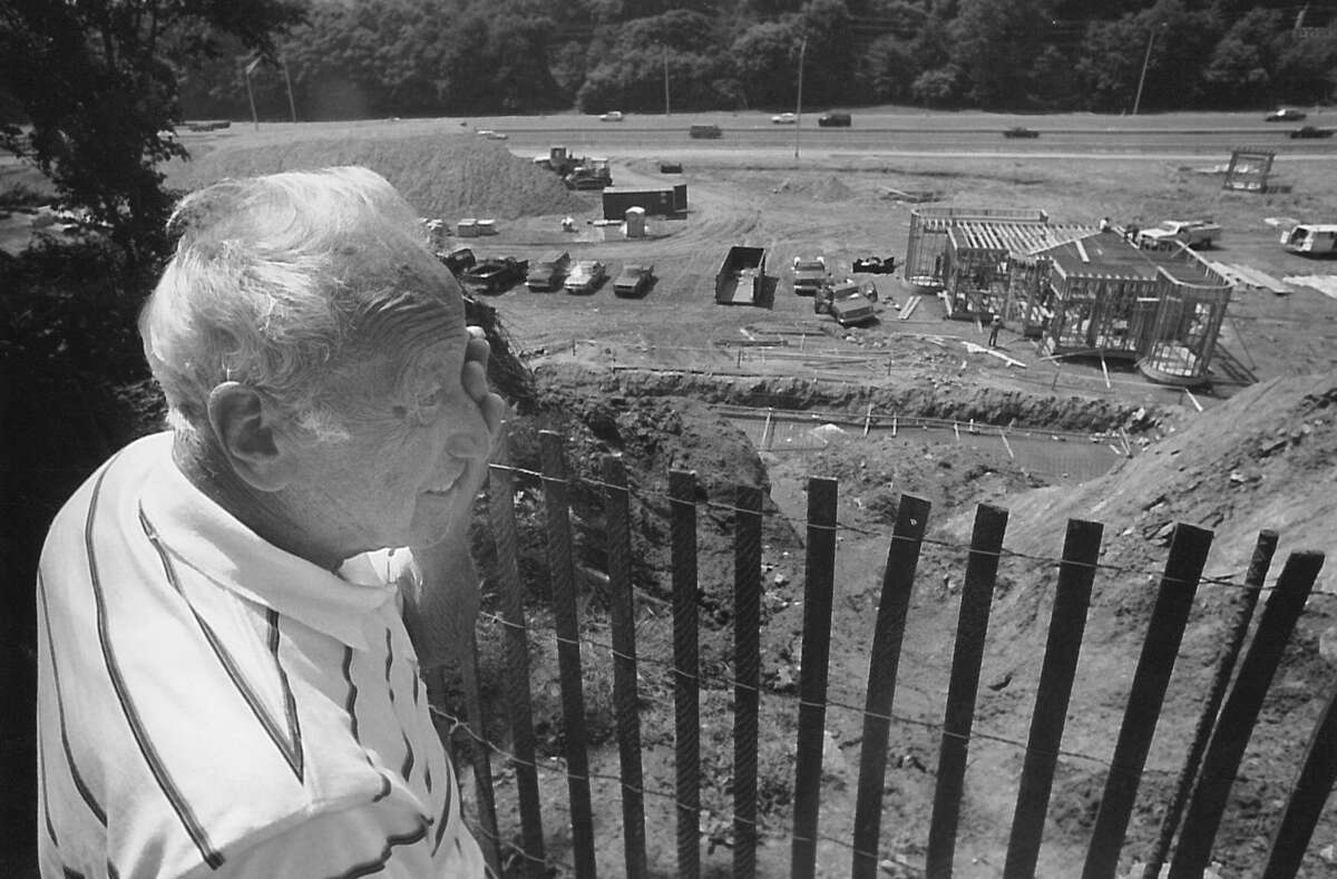 Frank Borchetta looks over the edge of his property overlooking the construction site for a new state truck weigh station in Greenwich on June 19, 1990.