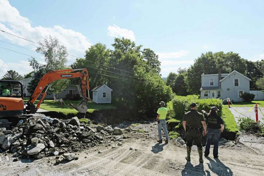 Crews work to repair a section of Church Street and what was once a lawn along side the road on Sunday, July 2, 2017, in Hoosick Falls, N.Y.  (Paul Buckowski / Times Union)
