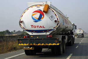 Fuel trucks branded with the Total SA logo pass along a road in Port Harcourt, Nigeria, on Friday, Jan. 15, 2016. With his security forces engaged in fighting Boko Haram's Islamist insurgency in the north, President Muhammadu Buhari can't afford renewed rebellion in the delta. Photographer: George Osodi/Bloomberg