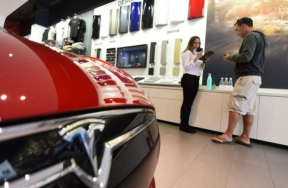 A Tesla Model 3 buyer (right) places an order in Santa Monica in 2015. Photo: ROBYN BECK, AFP/Getty Images
