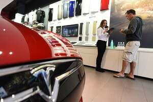 (FILES) This file photo taken on March 31, 2016 shows a sales reprsentative (L) helping a customer pre-order, the as yet unseen Tesla Model 3, in the Tesla store in Santa Monica, California. Tesla's first lower-priced Model 3 will come off the assembly line on July 7, 2017, two weeks early, CEO Elon Musk announced on July 3.  / AFP PHOTO / ROBYN BECKROBYN BECK/AFP/Getty Images