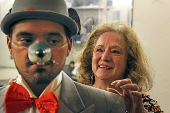 """Rose Kennedy looks over the costume she created for Alonzo Corona, who plays a tap-dancing rat among other characters in the Woodlawn Theatre's staging of """"Shrek."""""""