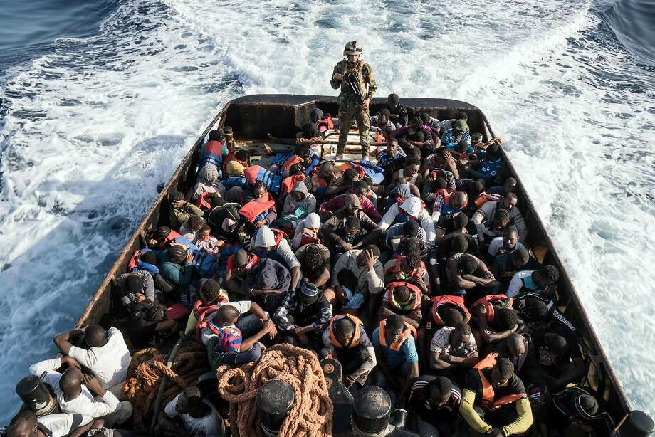 A Libyan coast guard officer watches over immigrants who were attempting to reach Europe last Tuesday. Photo: TAHA JAWASHI, AFP/Getty Images