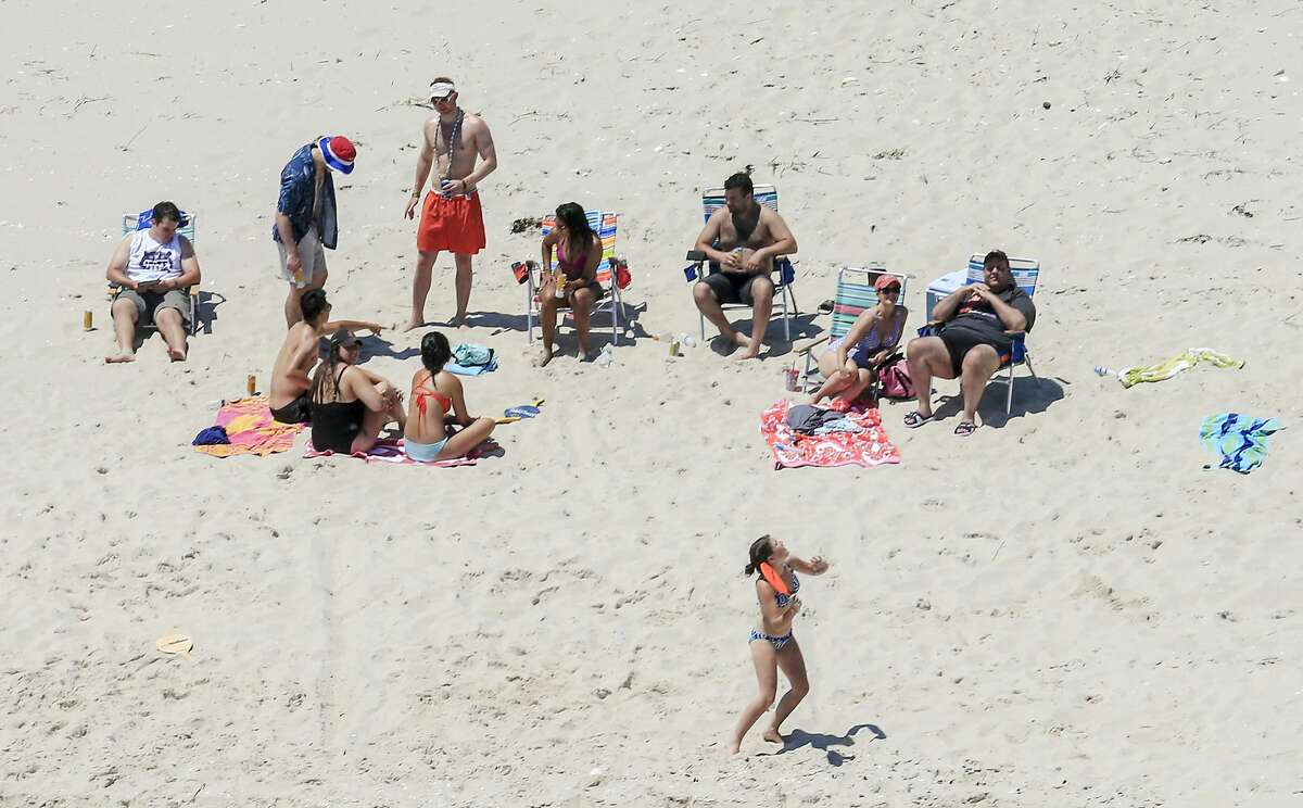 In this Sunday, July 2, 2017, photo, New Jersey Gov. Chris Christie, right, uses the beach with his family and friends at the governor's summer house at Island Beach State Park in New Jersey. Christie is defending his use of the beach, closed to the public during New Jersey's government shutdown, saying he had previously announced his vacation plans and the media had simply