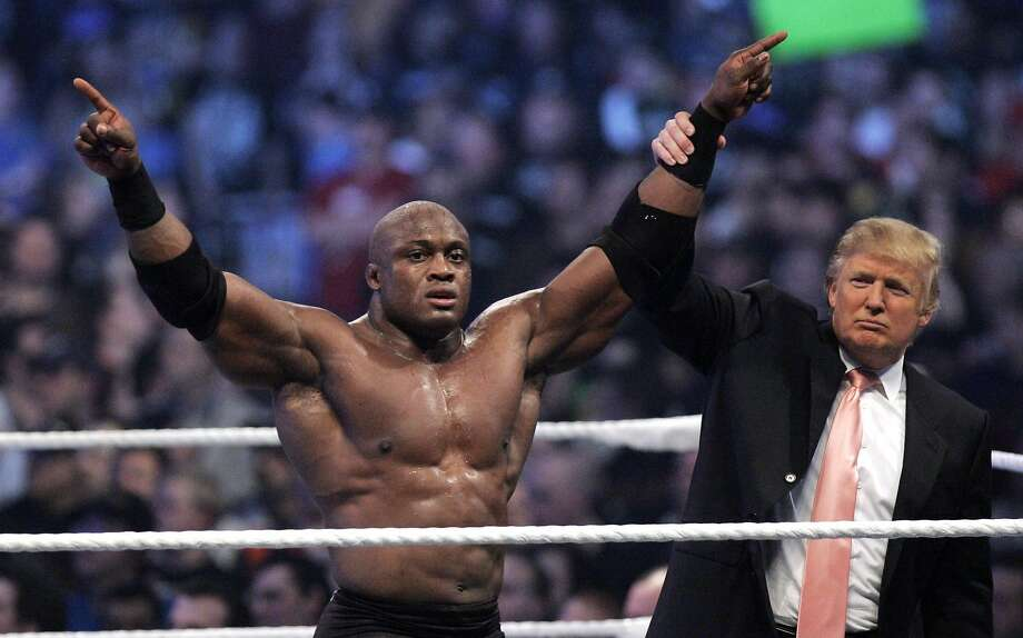 "FILE - In this Sunday, April 1, 2007, file photo, Donald Trump raises the arm of wrestler Bobby Lashley after he defeated Umaga at Wrestlemania 23 at Ford Field in Detroit. Trump body-slammed and then shaved the head of WWE boss Vince McMahon after what was known as the ""Battle of the Billionaires."" Wrestling aficionados say the president has, consciously or not, long borrowed the time-tested tactics of the game to cultivate the ultimate antihero character, a figure who wins at all costs, incites outrage and follows nobody's rules but his own. (AP Photo/Carlos Osorio, File) Photo: Carlos Osorio, Associated Press"
