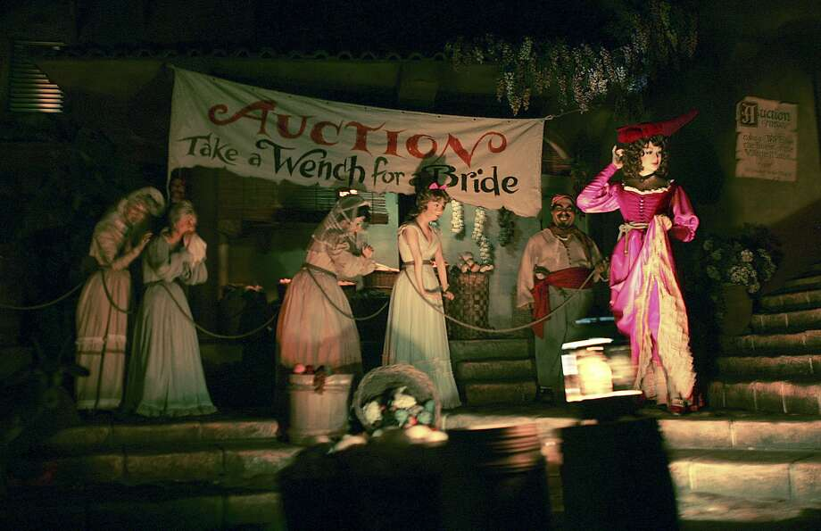 """This undated photo shows the scene where a bound and tearful woman is on the auction block for pirates to buy as a wife in Disneyland's Pirates of the Caribbean attraction in Anaheim, Calif. A banner that now says """"Auction, take a wench for a bride"""" will be changed to """"Auction, Surrender yer loot,"""" and the woman on the auction block will herself become a pirate. On Friday, June 30, 2017, Disneyland spokeswoman Suzi Brown said the changes will be made at the Paris park in July and at the Anaheim, California, and Florida parks in 2018. (Bruce Chambers/The Orange County Register via AP) Photo: Bruce Chambers, Associated Press"""