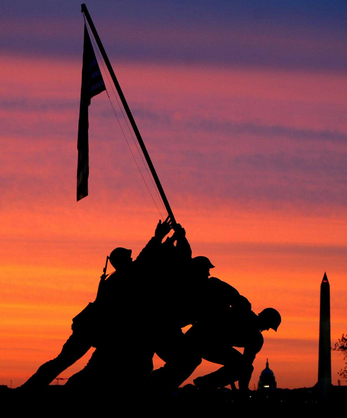 The sun rises behind the Iwo Jima Memorial in this May 5, 2003, file photo.