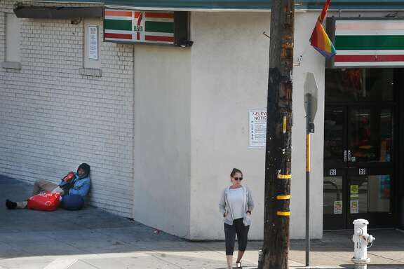 A man sits on the sidewalk next to a 7-11 store at 18th and Noe streets in San Francisco, Calif. on Saturday, July 1, 2017.