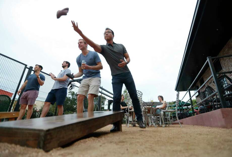 James Zhao, Right, And David Skahn, Left, Play Corn Hole Outside On