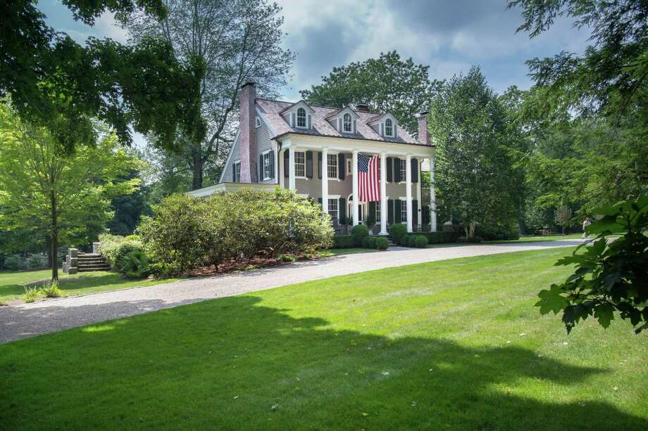 The two-story covered front porch of the antique Federal colonial house at 208 Canoe Hill Road displays the American flag, not just for the Fourth of July but throughout the year.