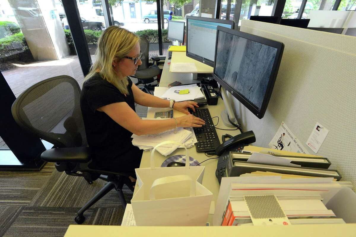 OFI sales associate Lone Albertsen works at her desk in OFI's new offices at 1010 Washington Blvd., in downtown Stamford, on Thursday, June 29, 2017.