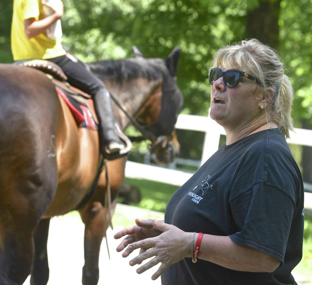Kelly Stackpole, of Moonlight Farms, in Redding, works with a rider during summer camp. Stackpole also is running Rising Starr Horse Rescue which rescues horses and helps children, teens and adults develop self confidence though riding. Monday, July 3, 2017, in Redding, Conn.