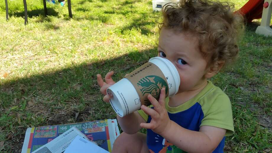 """Milo pretends to drink coffee like his daddy, who he calls """"Mama."""""""