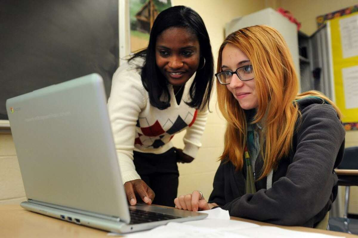 English teacher Amanda Palmer helps Vadia Medina log onto her Chromebook in a senior English class at Harding High School in Bridgeport in 2013. The portable deviceswill be replaced with Probooks in Bridgeport classrooms in 2018.