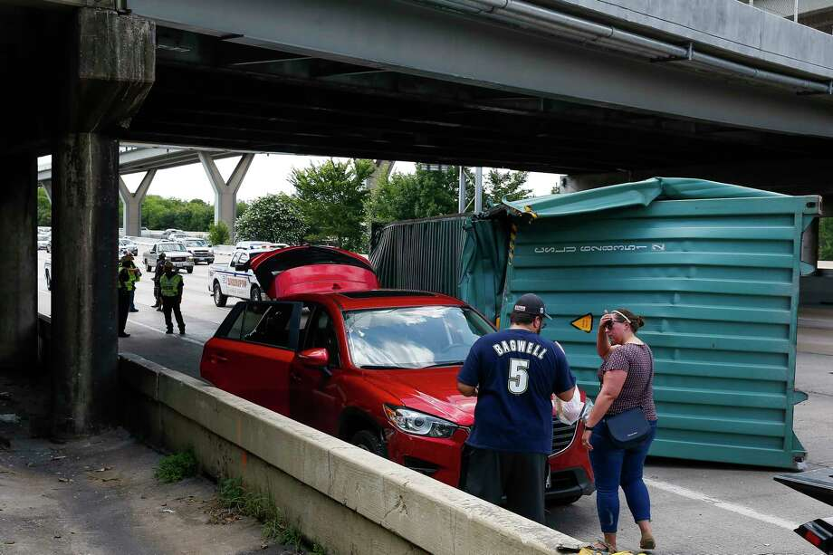 Josh Prater, left, and his fiancee, Tracy Lambert, stand by Lambert's car, which was hit by a shipping container that fell off a truck when it crashed into the Houston Avenue overpass while traveling eastbound on Interstate 10 on July 3. Photo: Michael Ciaglo, Houston Chronicle / Michael Ciaglo