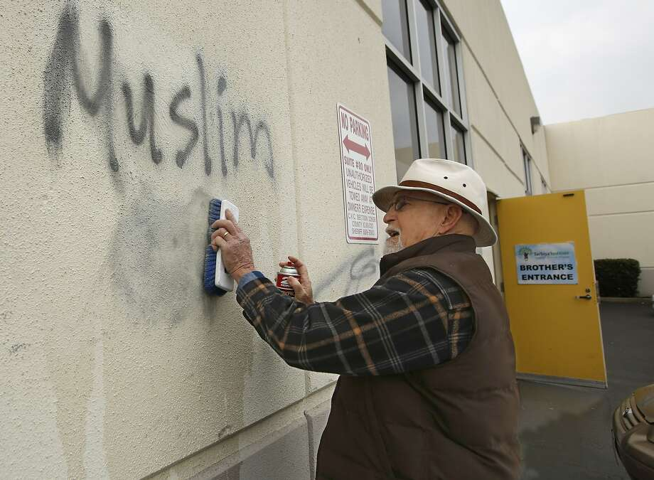 FILE - In this Feb. 1, 2017 file photo, Tom Garing cleans up racist graffiti painted on the side of a mosque in what officials are calling an apparent hate crime in Roseville, Calif. California's attorney general says the number of hate crimes increased about 11 percent last year, the second consecutive double-digit increase after years of decline. The report released Monday, July 3, 2017, shows 931 hate crimes statewide in 2016, nearly 100 more than in 2015. (AP Photo/Rich Pedroncelli, File) Photo: Rich Pedroncelli, Associated Press