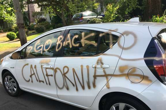 Gold-colored graffiti covers the house and car of Portland transplants Jessica Faraday and Preston Page. The couple moved to Oregon from Southern California in February and found their property vandalized Sunday morning.