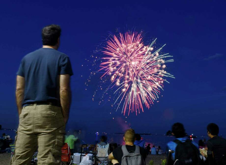 Folks watch fireworks at the Norwalk Independence Day fireworks celebration at Calf Pasture Beach in Norwalk, Conn. Monday, July 3, 2017. In addition to the colorful fireworks display, the program included a kids magic and music show by The Amazing Andy, a DJ set from DJ Nuzzo, and music from blues-rockers Southside Johnny and the Asbury Jukes. Photo: Tyler Sizemore, Hearst Connecticut Media / Greenwich Time