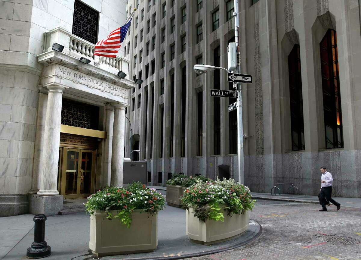 FILE - In this Monday, Aug. 24, 2015, file photo, a man walks towards the New York Stock Exchange. U.S. stocks are rising, Monday, July 3, 2017, as banks like Wells Fargo and Morgan Stanley make gains. Automakers are mostly higher as they start to report their monthly sales totals. Bankrate jumped after it agreed to be acquired by Red Ventures. (AP Photo/Seth Wenig, File)