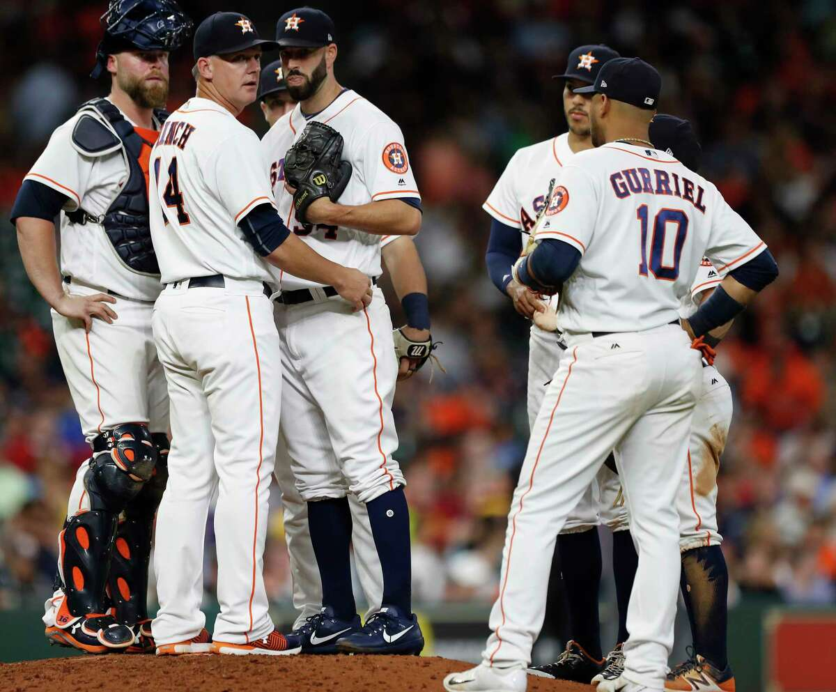 Astros manager A.J. Hinch (14) has been to the mound a lot lately, with Mike Fiers, right, the only starter in the last 14 games to make it through six innings.