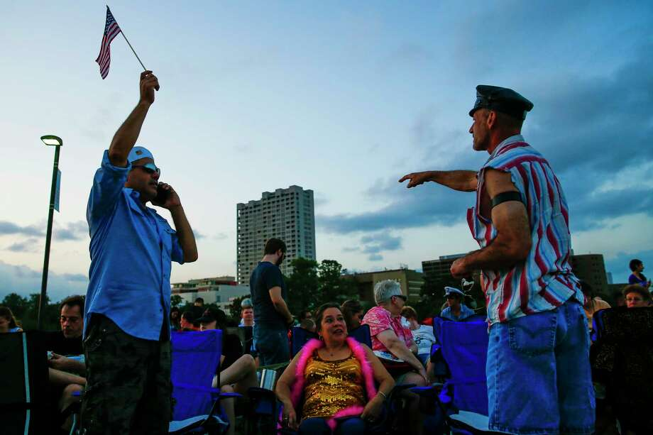Jesse Miranda, left, and Chris James, right, wave down friends as they wait for the Village People to perform at the Miller Outdoor Theater Monday, July 3, 2017 in Houston. Photo: Michael Ciaglo, Houston Chronicle / Michael Ciaglo