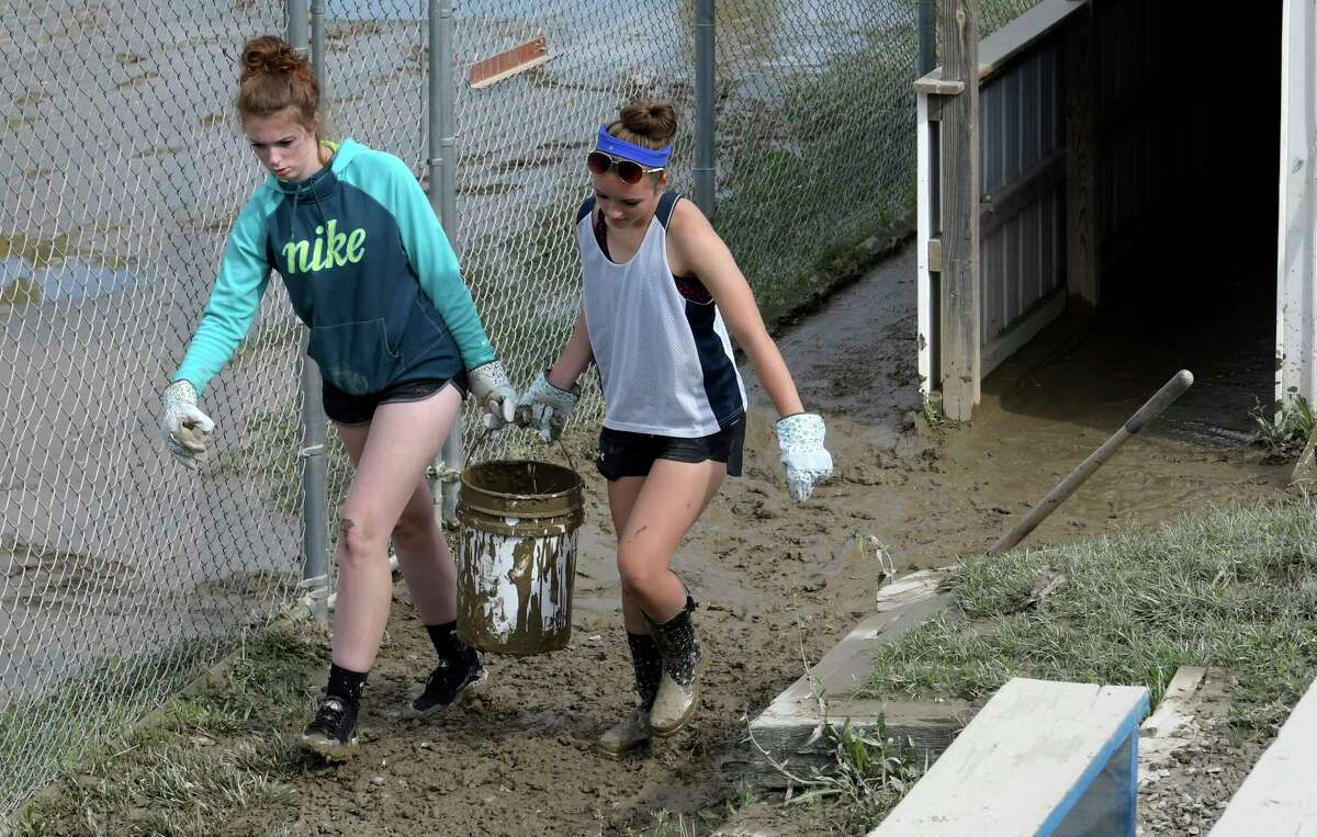 Continue viewing the slideshow to see other disasters in Capital Region history. Flooding:Breanna Breuenstuhl, 18, left and Cecilia Vincent, 17 help each other carry a bucket of mud that was removed from the dugout at the Hoosick Falls Baseball and Softball field Monday July 3, 2017 in Hoosick Falls, N.Y. The duo of former players volunteered to help rehab the field after a storm flooded the fields which will be used this weekend for a large softball tournament. (Skip Dickstein/Times Union)