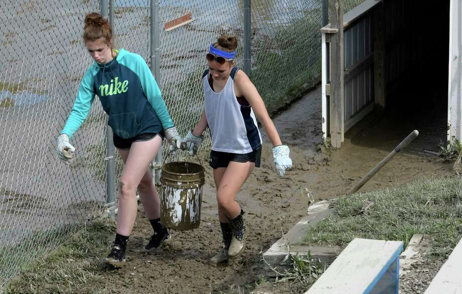 Continue viewing the slideshow to see other disasters in Capital Region history.Flooding: Breanna Breuenstuhl, 18, left and Cecilia Vincent, 17 help each other carry a bucket of mud that was removed from the dugout at the Hoosick Falls Baseball and Softball field Monday July 3, 2017 in Hoosick Falls, N.Y.  The duo of former players volunteered to help rehab the field after a storm flooded the fields which will be used this weekend for a large softball tournament. (Skip Dickstein/Times Union) Photo: SKIP DICKSTEIN / 20040969A