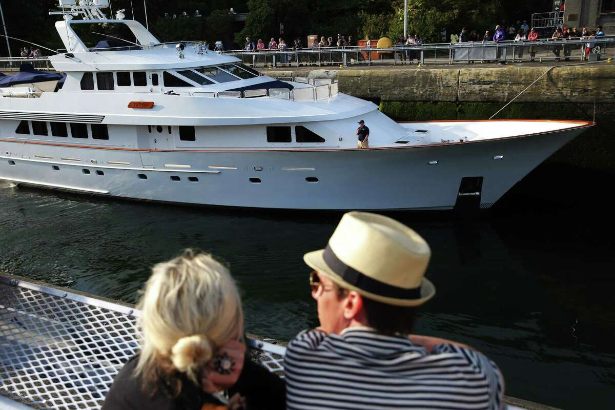 People watch boats pass through the Hiram M. Chittenden Ballard Locks, during a holiday weekend celebration held in honor of the Locks' Centennial anniversary, July 3, 2017. The Locks are the nation's busiest, passing over 40,000 vessels through their gates every year.