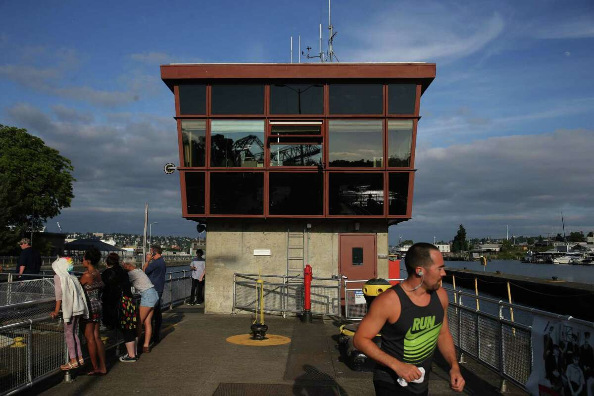 People walk over the Hiram M. Chittenden Ballard Locks, during a holiday weekend celebration held in honor of the Locks' Centennial anniversary, July 3, 2017. The Locks are the nation's busiest, passing over 40,000 vessels through their gates every year.