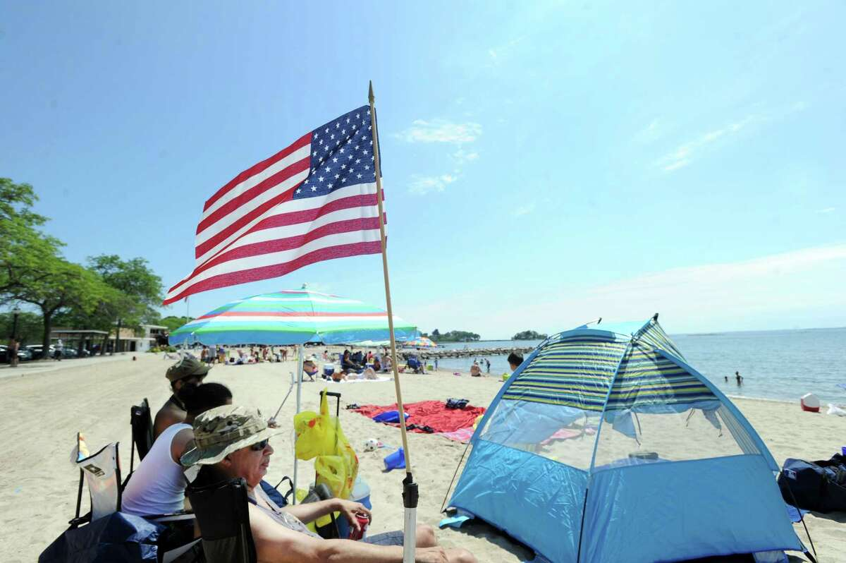 At left, Ben Marrero of the Bronx, N.Y., flew an American Flag that was attached to his beach chair while enjoying the beautiful weather with friends on the Fourth of July at Cummings Park beach in Stamford, Conn., Tuesday, July 4, 2017.