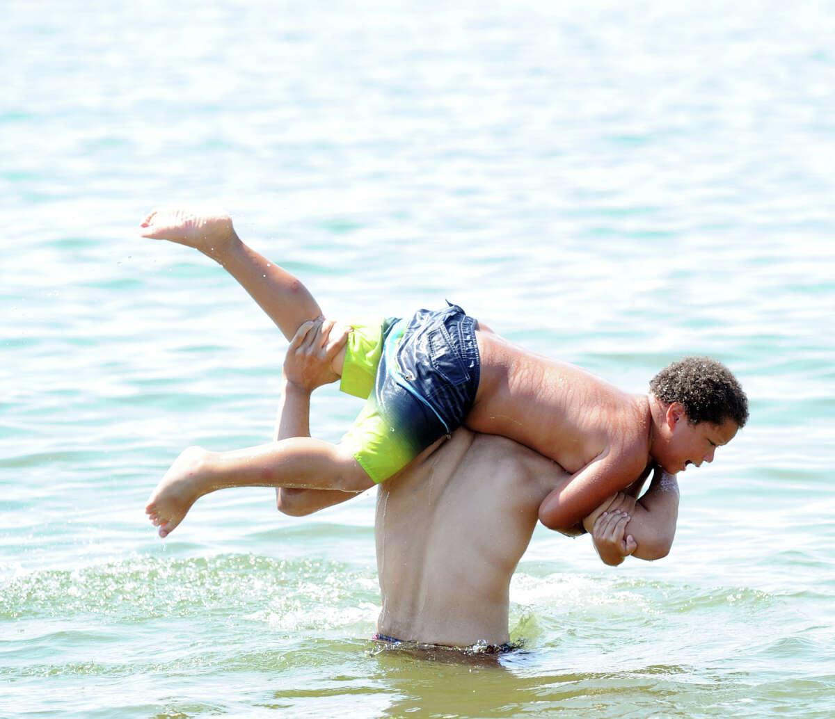 Stamford resident Kadnn Anthony Pena, top, just before he got tossed into the water by friend Joseph Muniz, also of Stamford, on the Fourth of July at Cummings Park beach in Stamford, Conn., Tuesday, July 4, 2017.