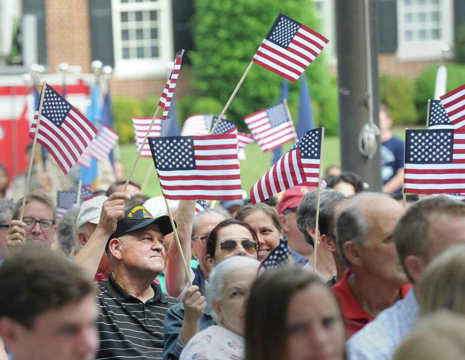 At left wearing a black cap, Greenwich resident Tom Nelson waves an American Flag along with others who attended the Fourth of July ceremony at Greenwich Town Hall, Greenwich, Conn., Tuesday morning, July 4th, 2017. Photo: Bob Luckey Jr. / Hearst Connecticut Media / Greenwich Time